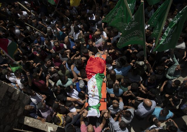 Palestinian mourners carry the body of Rasheed Abu Arra who was killed in the clashes with Israeli forces during his funeral, in the Village of Aqqaba near the West Bank town of Tubas, Wednesday, May 12, 2021.