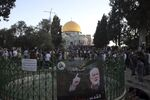 A banner depicting Hamas' supreme leader Ismail Haniyeh is on display as Muslims gather for Eid al-Fitr prayers at the Dome of the Rock Mosque in the Al-Aqsa Mosque compound in the Old City of Jerusalem, Thursday, May 13, 2021.