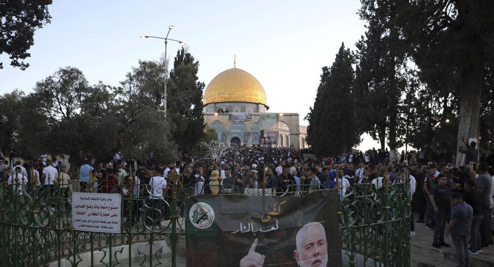 A banner depicting Hamas' leader Ismail Haniyeh is on display as Muslims gather for the Eid al-Fitr prayers at the Dome of the Rock Mosque in the Al-Aqsa compound in Jerusalem's Old City on Thursday 13 May 2021.