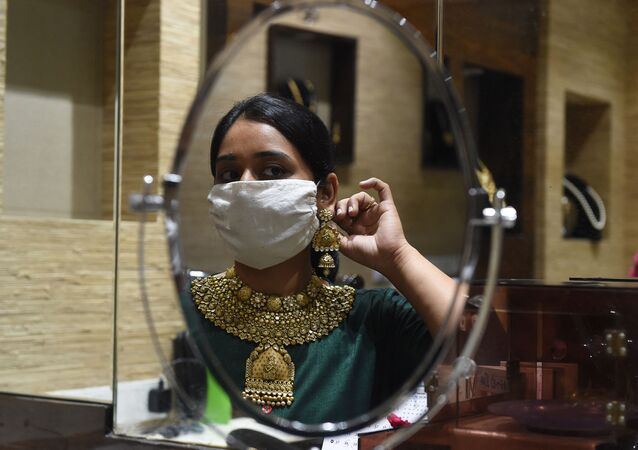 A customer wearing a face mask as a preventive measure against the COVID-19 coronavirus, looks at herself in the mirror while trying on gold jewellery in an Ahmedabad shop on 31 July 2020.