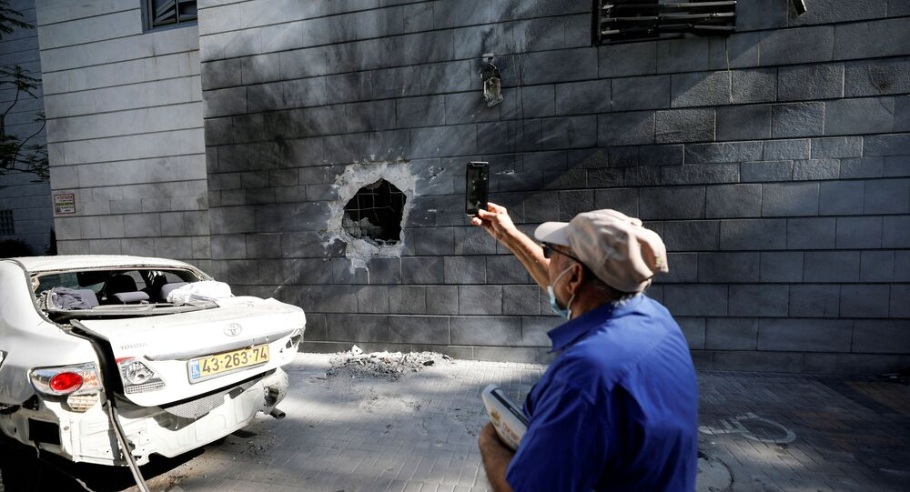 An Israeli man takes a photo with his mobile phone at a residential building after a rocket launched overnight from the Gaza Strip hit it in Ashkelon, Israel May 14, 2021.
