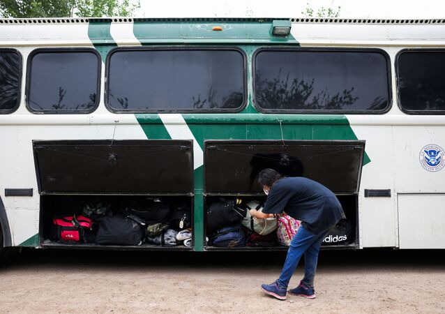 A migrant from Venezuela loads her belongings onto a border patrol bus after crossing the Rio Grande river into the United States from Mexico in Del Rio, Texas, U.S., May 11, 2021