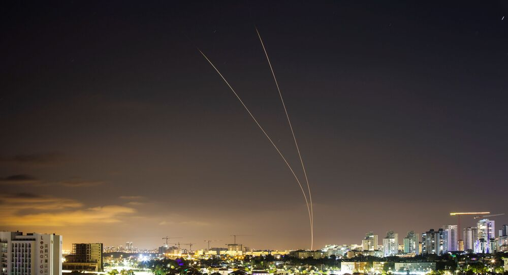 Streaks of light are seen as Israel's Iron Dome anti-missile system aims to intercept rockets launched from the Gaza Strip towards Israel, as seen from Ashkelon, Israel, 14 May 2021.