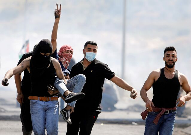 An injured Palestinian demonstrator gestures as he is evacuated during clashes with Israeli forces at a protest over tension in Jerusalem and Israel-Gaza escalation, near Hawara checkpoint near Nablus in the Israeli-occupied West Bank, May 14, 2021.