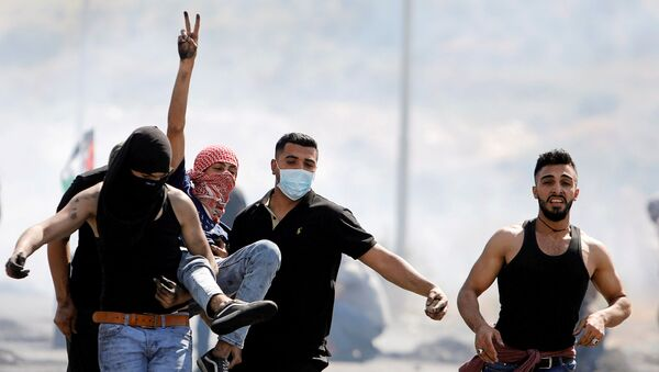 An injured Palestinian demonstrator gestures as he is evacuated during clashes with Israeli forces at a protest over tension in Jerusalem and Israel-Gaza escalation, near Hawara checkpoint near Nablus in the Israeli-occupied West Bank, May 14, 2021. - Sputnik International