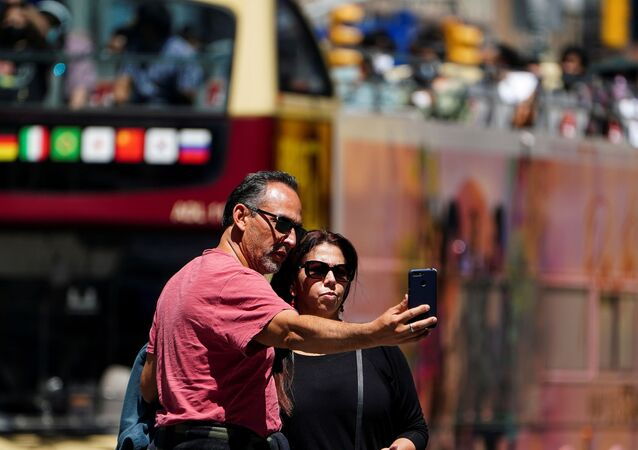 People with no masks pose for photos in Times Square during the coronavirus disease (COVID-19) pandemic in the Manhattan borough of New York City, New York, U.S., May 14, 2021