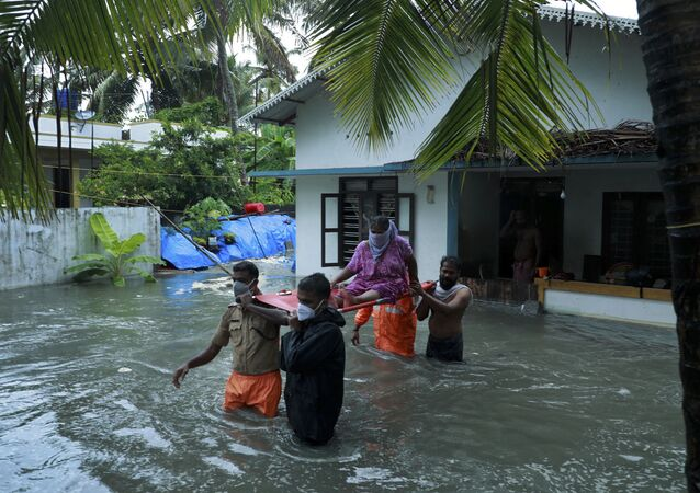 Police and rescue personnel evacuate local residents from a flooded house in a coastal area after heavy rains under the influence of cyclone 'Tauktae' in Kochi on May 14, 2021.