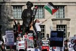 Pro-Palestine demonstrators hold placards and wave flags during a protest opposite the entrance to Downing Street in central London on May 15, 2018.