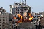 A ball of fire erupts from the Jala Tower as it is destroyed in an Israeli airstrike in Gaza city controlled by the Palestinian Hamas movement, on 15 May 2021.