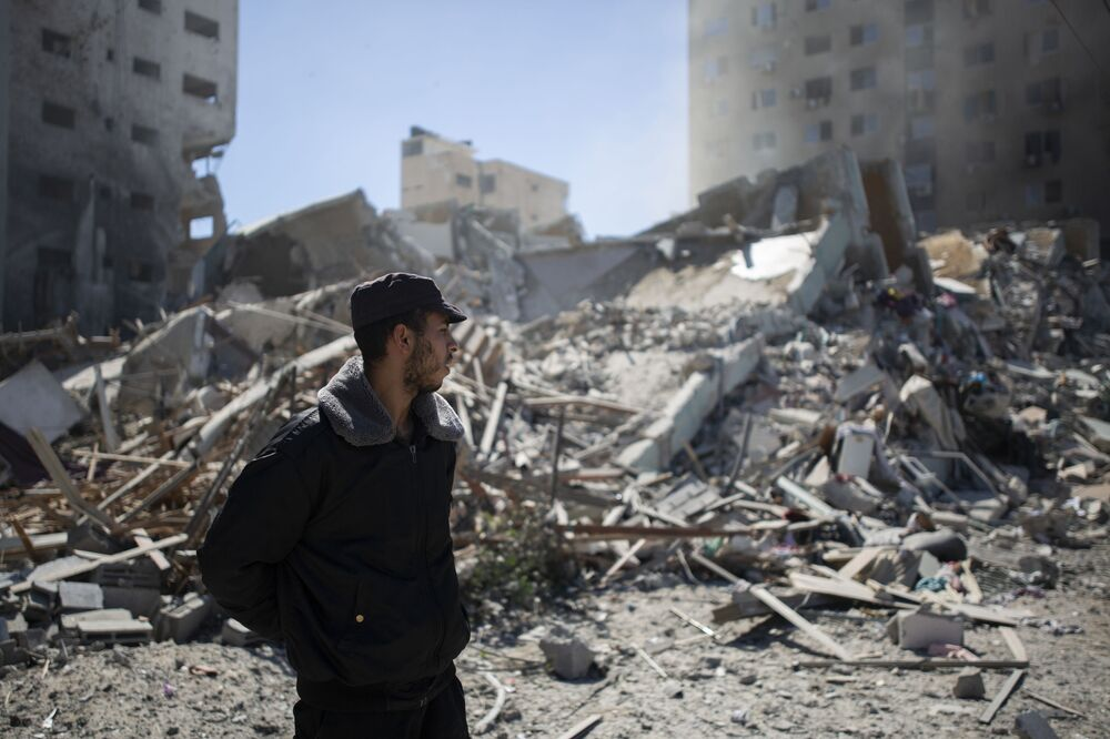 A Palestinian policeman stands in the rubble.