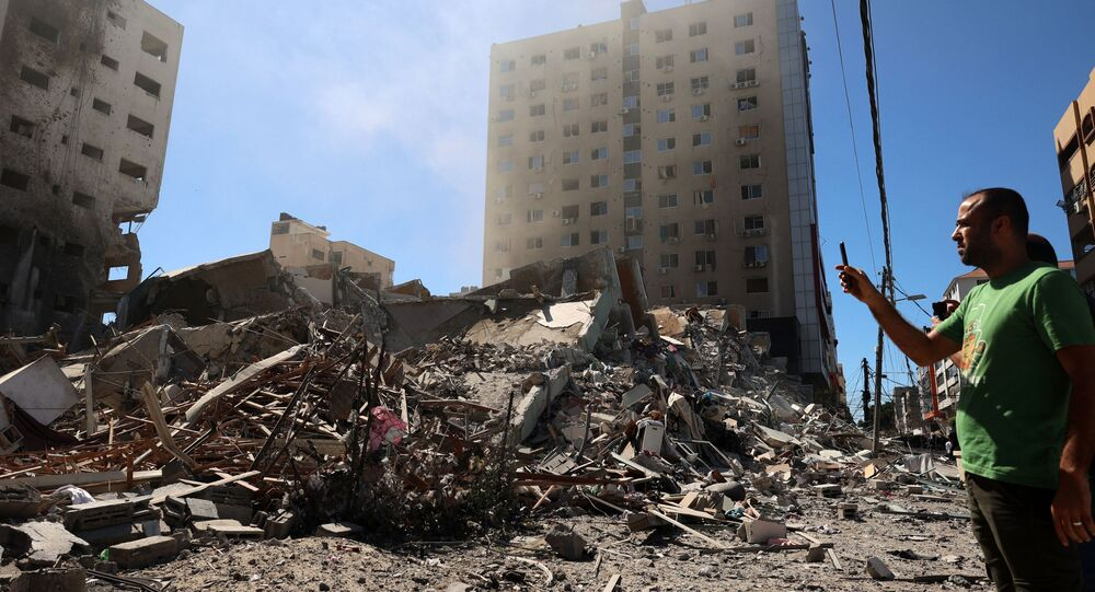 A Palestinian man takes a photograph with his mobile phone of a building hit and destroyed during an Israeli Air strike in Gaza City, on 15 May 2021.