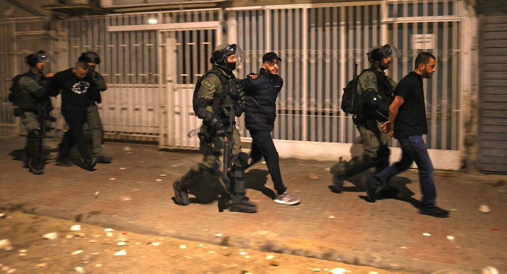 Israeli forces detain a group of Arab-Israelis in the mixed Jewish-Arab city of Lod on May 13, 2021, during clashes between Israeli far-right extremists and Arab-Israelis.