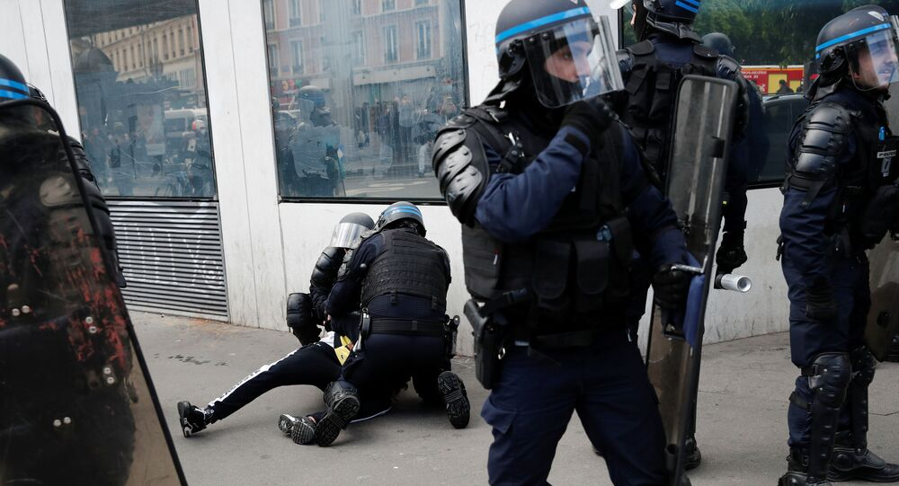 Police officers detain a man during a protest in support of Palestinians following a flare-up of Israeli-Palestinian violence, in Paris, France, May 15, 2021.