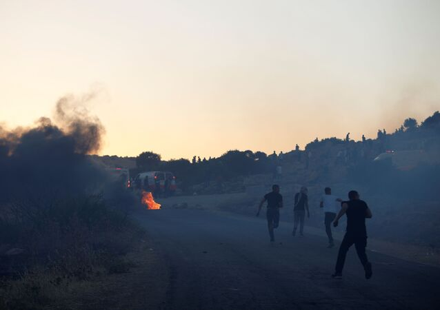 Palestinian demonstrators run towards an ambulance during a protest over tension in Jerusalem and Israel-Gaza escalation, near Tubas in the Israeli-occupied West Bank, May 15, 2021.