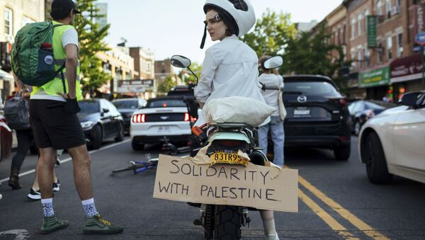 An Activist sits on her scooter as thousands of activists supporting Palestine converge in Brooklyn Saturday, May 15, 2021, in New York. - Sputnik International