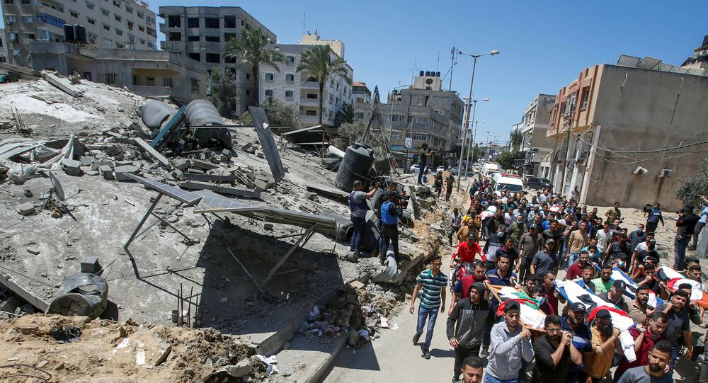 Mourners carry the bodies of Palestinians, including members of Abu Hatab family, who were killed amid a flare-up of Israeli-Palestinian violence, during their funeral near the remains of a building destroyed in Israeli air strikes, at the Beach refugee camp, in Gaza City May 15, 2021.
