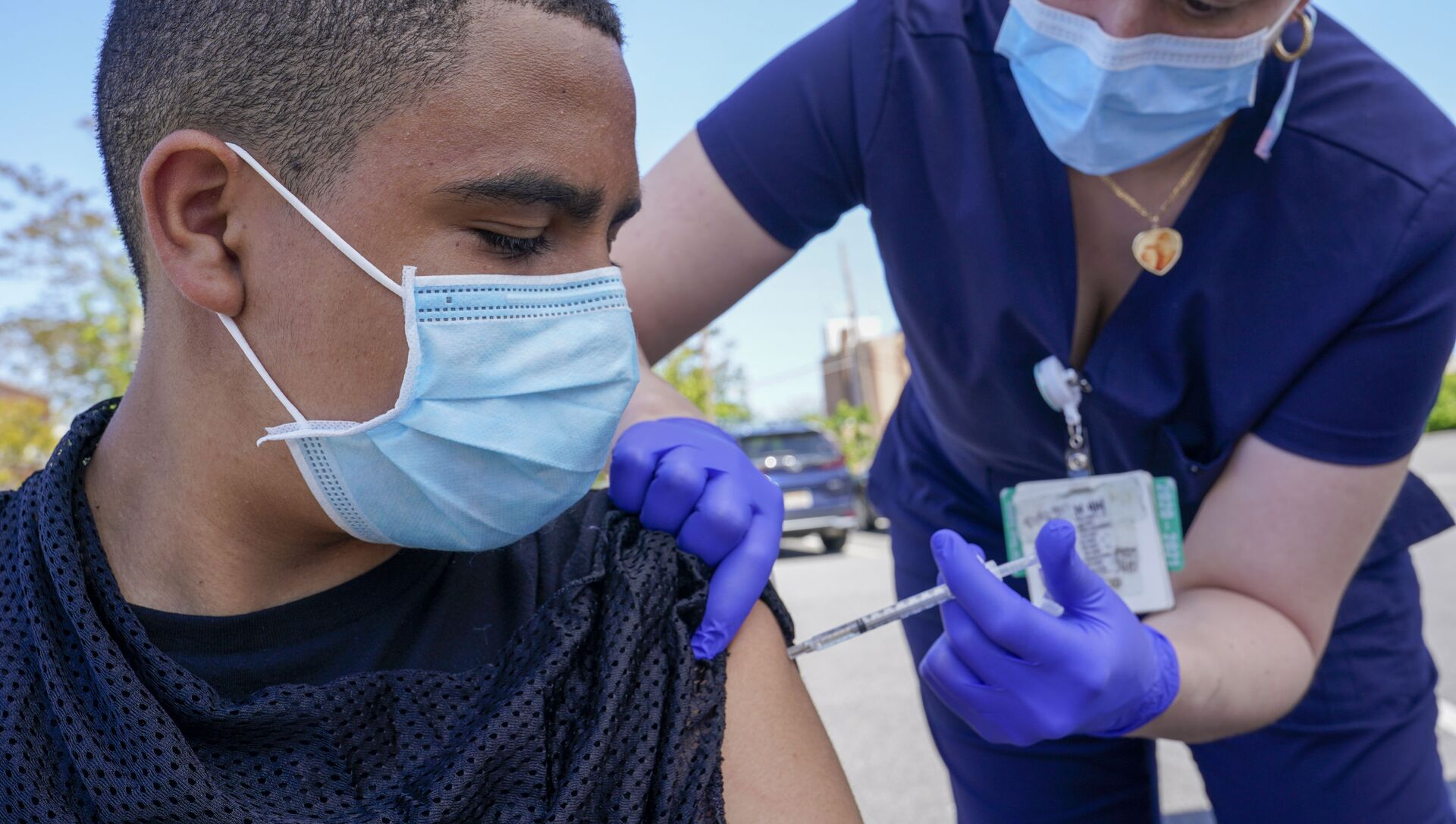 Justin Bishop, 13, watches as Registered Nurse Jennifer Reyes inoculates him with the first dose of the Pfizer COVID-19 vaccine at the Mount Sinai South Nassau Vaxmobile parked at the De La Salle School, Friday, 14 May 2021, in Freeport, NY. - Sputnik International, 1920, 23.07.2021