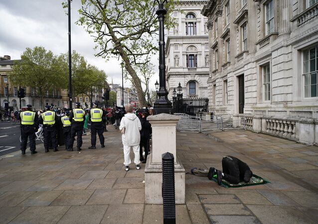 A man prays as people gather outside Downing Street to protest against Israeli attacks on Palestinians in Gaza, in London, Saturday, 15 May 2021