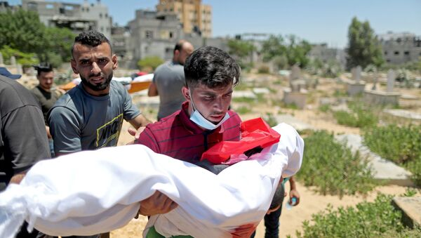 A man carries the body of a Palestinian child from Al-Hadidi family, who was killed amid a flare-up of Israeli-Palestinian violence, during their funeral at a cemetery in the northern Gaza Strip May 15, 2021. - Sputnik International