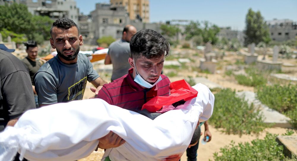 A man carries the body of a Palestinian child from Al-Hadidi family, who was killed amid a flare-up of Israeli-Palestinian violence, during their funeral at a cemetery in the northern Gaza Strip May 15, 2021.