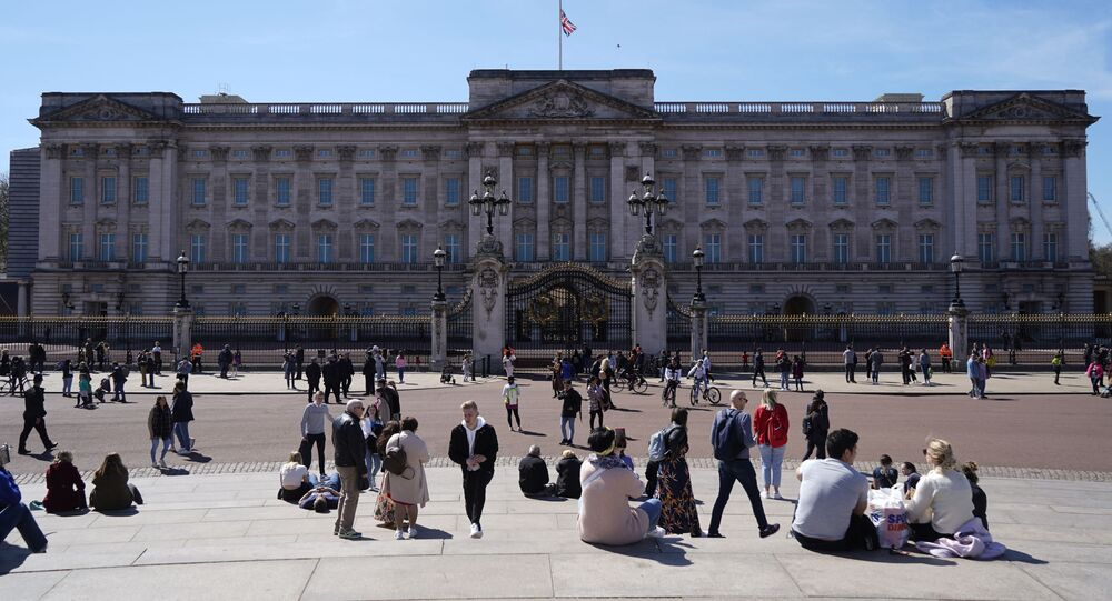 People sit outside Buckingham Palace in central London on April 17, 2021, ahead of the funeral for Britain's Prince Philip, Duke of Edinburgh.