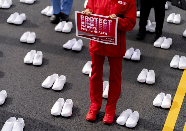 Nurses stand surrounded by white pairs of shoes to represent the 402 nurses who died because of covid-19, near the White House in Washington, Wednesday, May 12, 2021