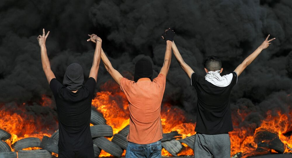Palestinian demonstrators look at burning tires during a protest over tension in Jerusalem and Israel-Gaza escalation, in the Israeli-occupied West Bank, May 16, 2021.