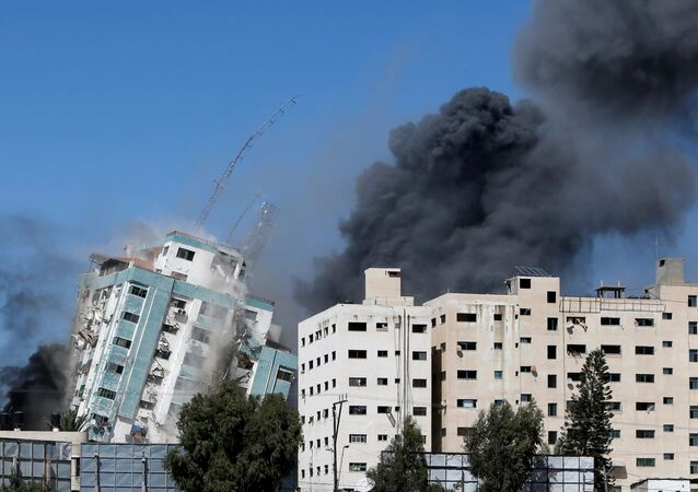 A tower housing AP, Al Jazeera offices collapses after Israeli missile strikes in Gaza city, May 15, 2021.
