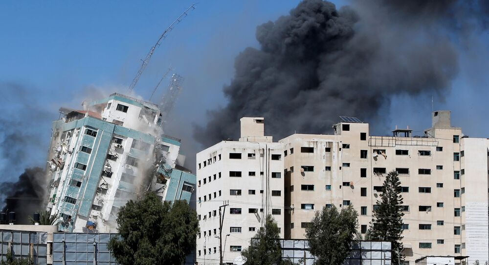 A tower housing AP, Al Jazeera offices collapses after Israeli missile strikes in Gaza city, 15 May 2021.