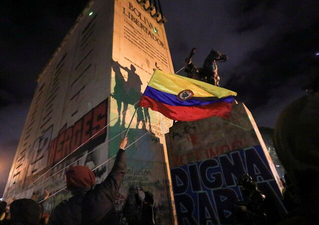 People try to topple the statue of South American independence leader Simon Bolivar during a protest against sexual assault by the police and the excess of public force against peaceful protests, in Bogota, Colombia, May 15, 2021.