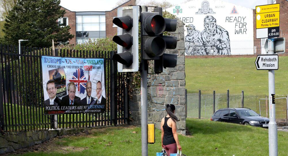 A woman walks past a pro-Loyalist, anti-Northern Ireland Protocol poster (L) in Belfast on April 19, 2021