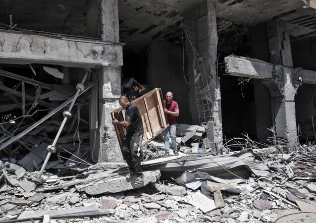 Palestinian men remove salvageable items from the bombarded Al-Jawhara Tower in Gaza City on May 17, 2021, five days after it was targeted by Israeli airstrikes.