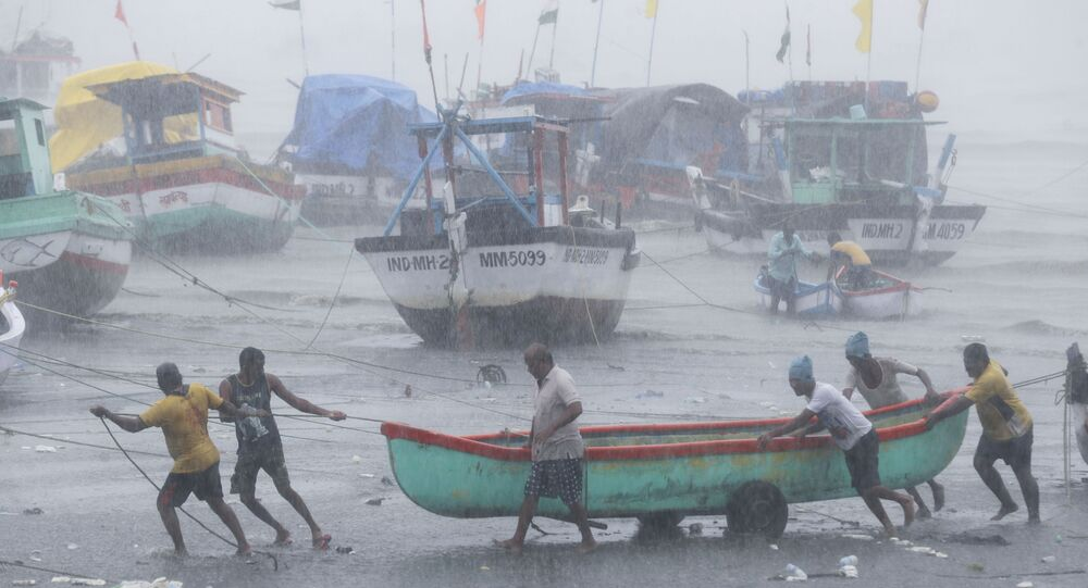 Fishermen try to move a fishing boat to a safer ground on the Arabian Sea coast in Mumbai, India, Monday, May 17, 2021