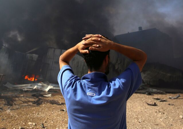 A man stands near a burning sponge factory after it was hit by Israeli artillery shells, according to witnesses, in the northern Gaza Strip May 17, 2021