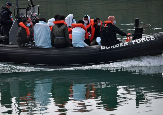 UK Border Force officials travel in a RIB with migrants picked up at sea whilst Crossing the English Channel, as they arrive at the Marina in Dover, southeast England on August 15, 2020