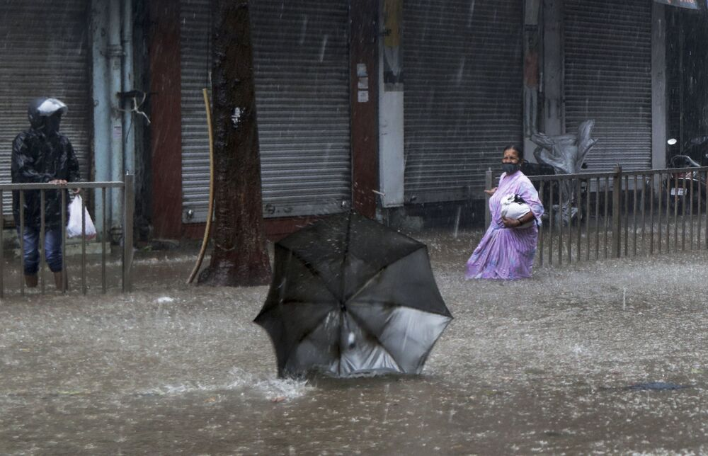 A woman helplessly watches her umbrella fly away in the wind during a heavy rain in Mumbai, India.