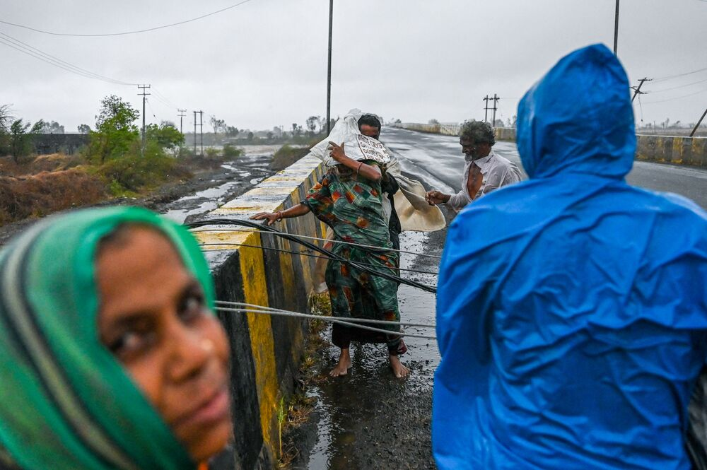 Villagers try to cross fallen down electricity cable on a bridge near Diu, after Cyclone Tauktae blasted ashore in western India late 17 May with fierce winds and drenching rains that turned streets into rivers, disrupting the country's response to its devastating Covid-19 outbreak.