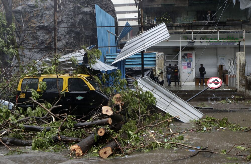 A taxi car that was damaged after a tree fell on it during a heavy rain in Mumbai, India.