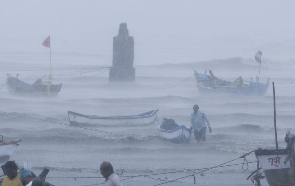 A fisherman waits for help as he tries to move a fishing boat to a safer ground on the Arabian Sea coast in Mumbai, India.
