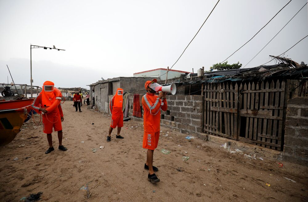 A member of the National Disaster Response Force (NDRF) uses a megaphone to appeal to residents to move to safer place ahead of Cyclone Tauktae in Veraval in the western state of Gujarat, India.