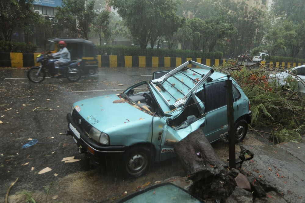 A damaged car is seen on a road after a tree fell on it due to strong winds caused by Cyclone Tauktae in Mumbai, India.