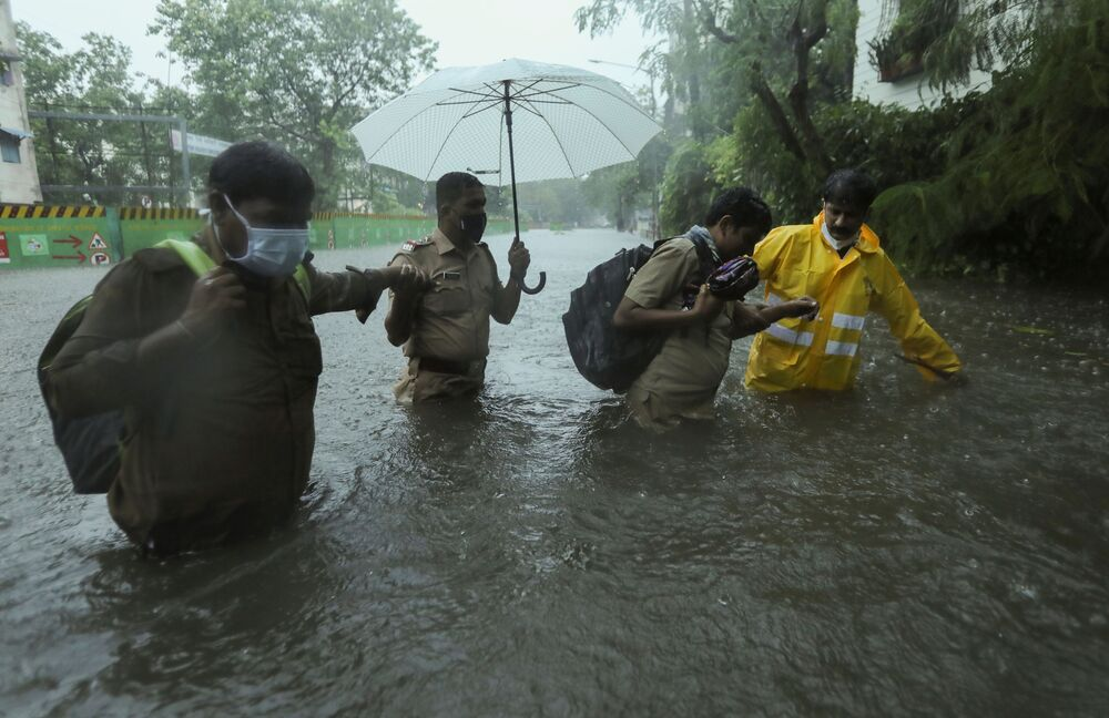 Frontline workers help people cross a flooded street after heavy rainfall caused by Cyclone Tauktae in Mumbai, India.
