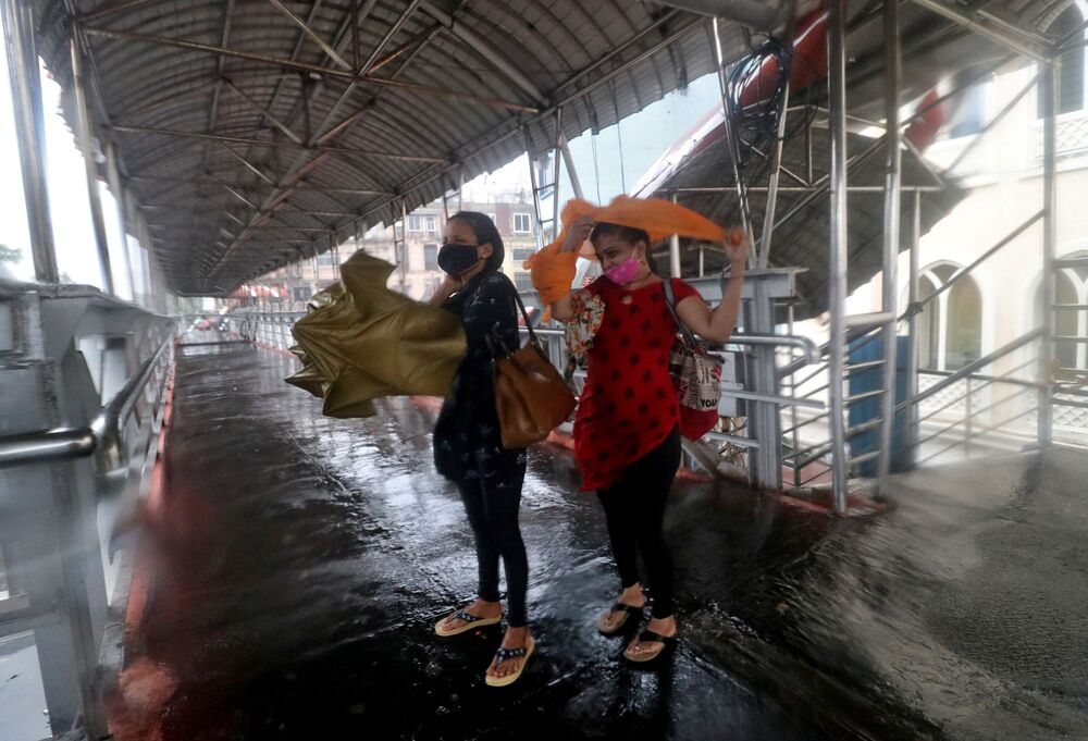 Women take shelter at a pedestrian overpass during heavy rains caused by Cyclone Tauktae in Mumbai, India.