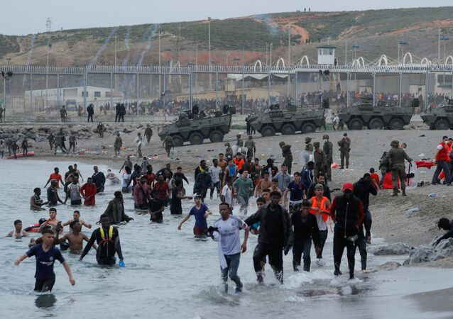 Moroccan citizens walk in the water as Spanish legionnaires patrol the area near the fence on a beach in El Tarajal, after thousands swam across the Spanish-Moroccan border on Monday, in Ceuta, Spain, May 18, 2021. REUTERS/Jon Nazca