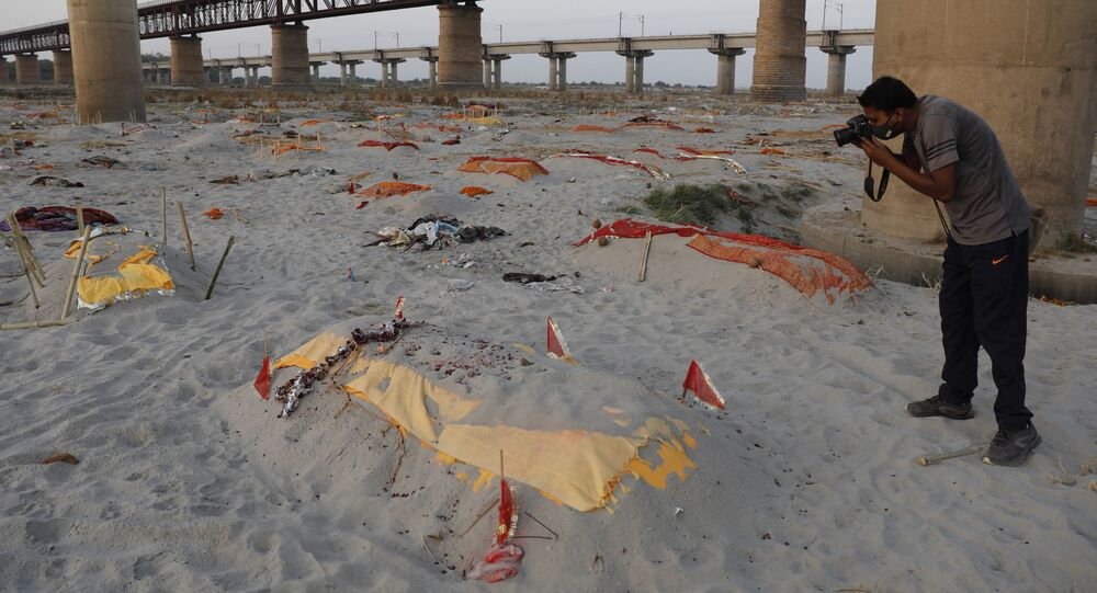 Suspected victims of COVID-19 are seen in shallow graves buried in the sand near a cremation ground on the banks of the Ganges River in Prayagraj, India on Saturday, 15 May 2021.