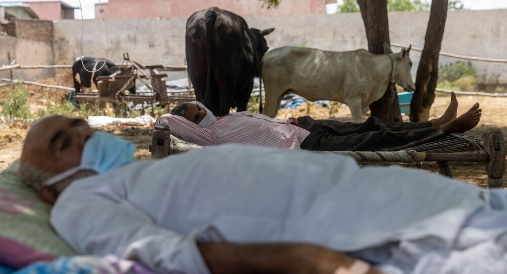 Villagers with breathing difficulties rest in cots as they receive treatment at a makeshift open-air clinic, amidst the spread of the coronavirus disease (COVID-19), in Mewla Gopalgarh village in Jewar district in the northern state of Uttar Pradesh, India, May 16, 2021
