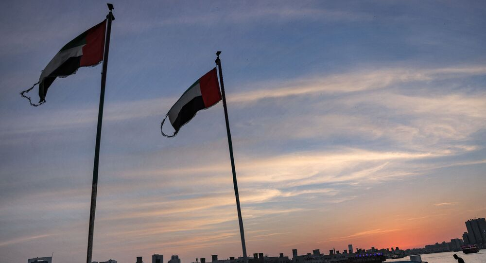 This picture taken on May 2, 2021 shows Emirati flags flying by boats moored along the Dubai creek at sunset. (Photo by GIUSEPPE CACACE / AFP)