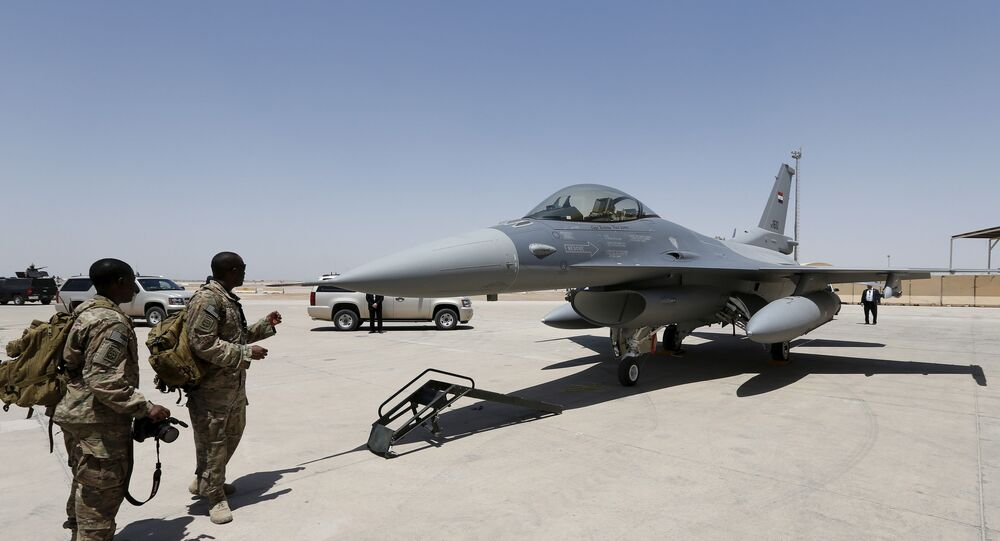 U.S. Army soldiers look at an F-16 fighter jet during an official ceremony to receive four such aircraft from the United States, at a military base in Balad, Iraq