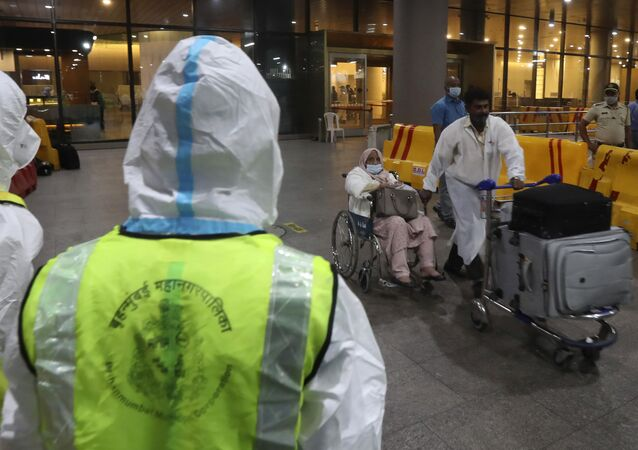 Indian municipal workers in personal protective equipment (PPE) watch as a passenger on wheelchair arrives from United Kingdom, at Chhatrapati Shivaji Maharaj International Airport in Mumbai, India, Tuesday, Dec. 22, 2020