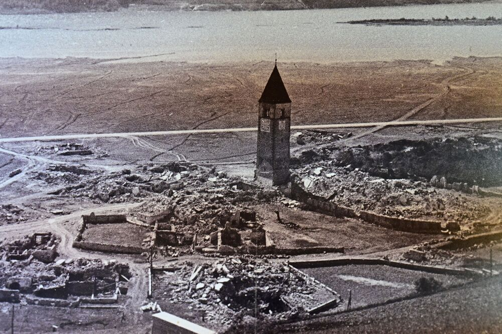 An aerial picture taken on 9 July 2020 in the museum of the new city of Curon Venosta (Graun im Vinschgau), some 100km north-west of Bolzano, northern Italy, shows a photograph of Curon's old bell tower as it was before being submerged in lake Resia.